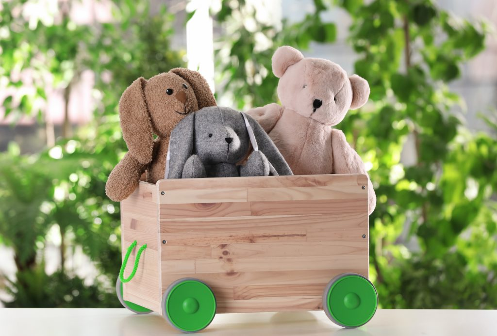 Wooden cart with stuffed toys on table