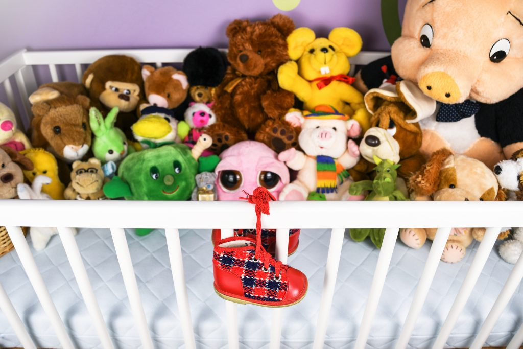 Group of colorful fluffy stuffed animal toys closeup with hanging red small baby shoe on a white crib fence
