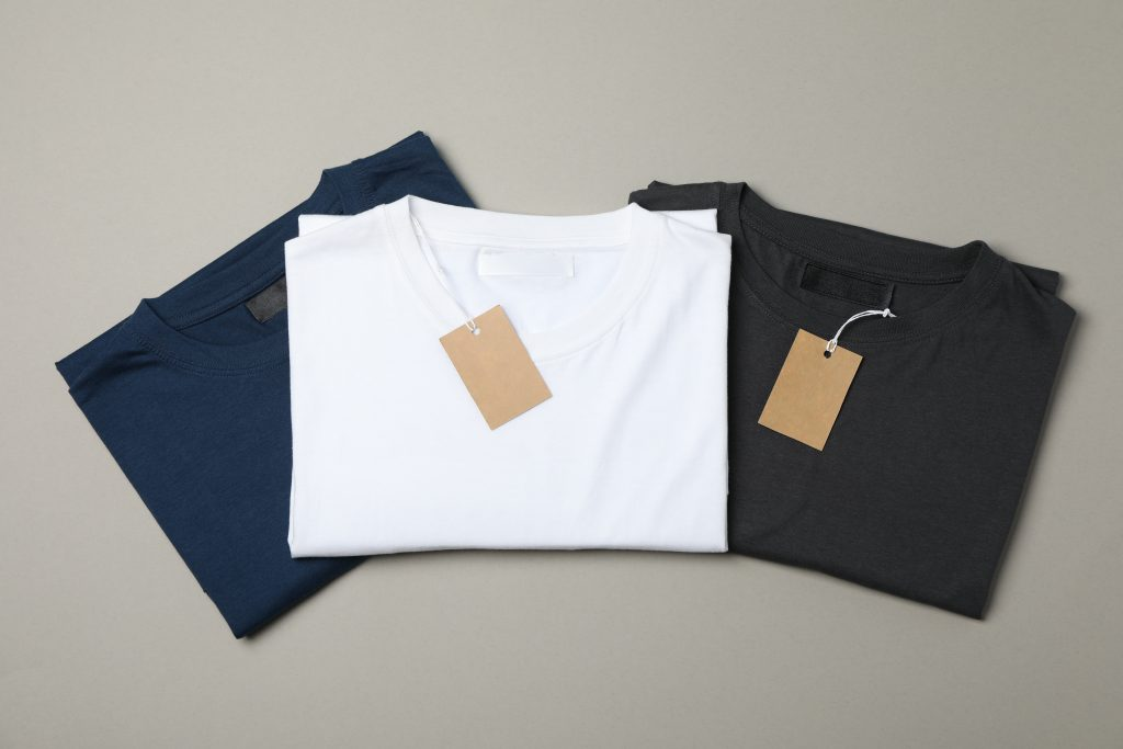 Folded blank t-shirts with tags on gray background, space for text