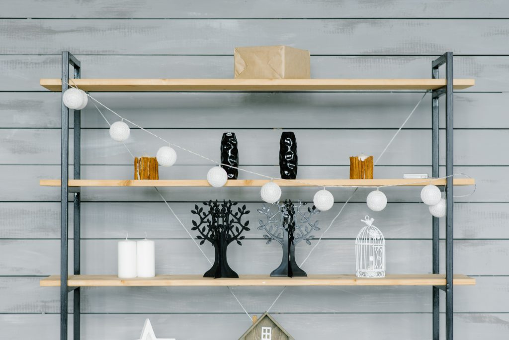Shelf with decorative elements in the living room in the house. Scandinavian minimalist style in the interior