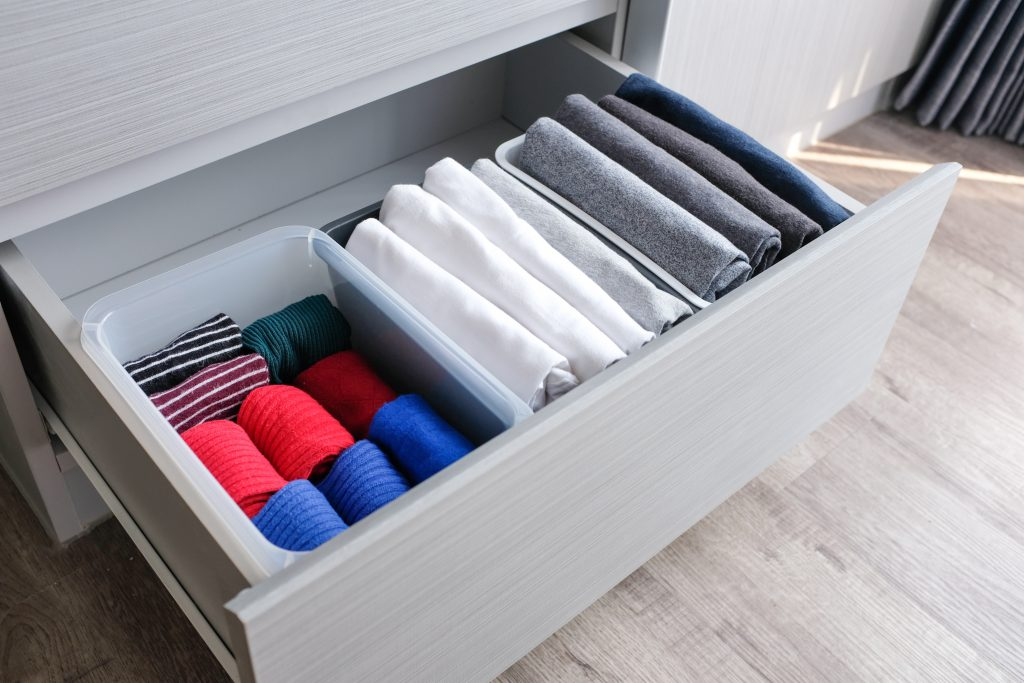 Close up stack of folded t shirt black gray white color and folded bright colorful socks in plastic baskets in a closet drawer in natural light. Room cleaning and tidying up concept.