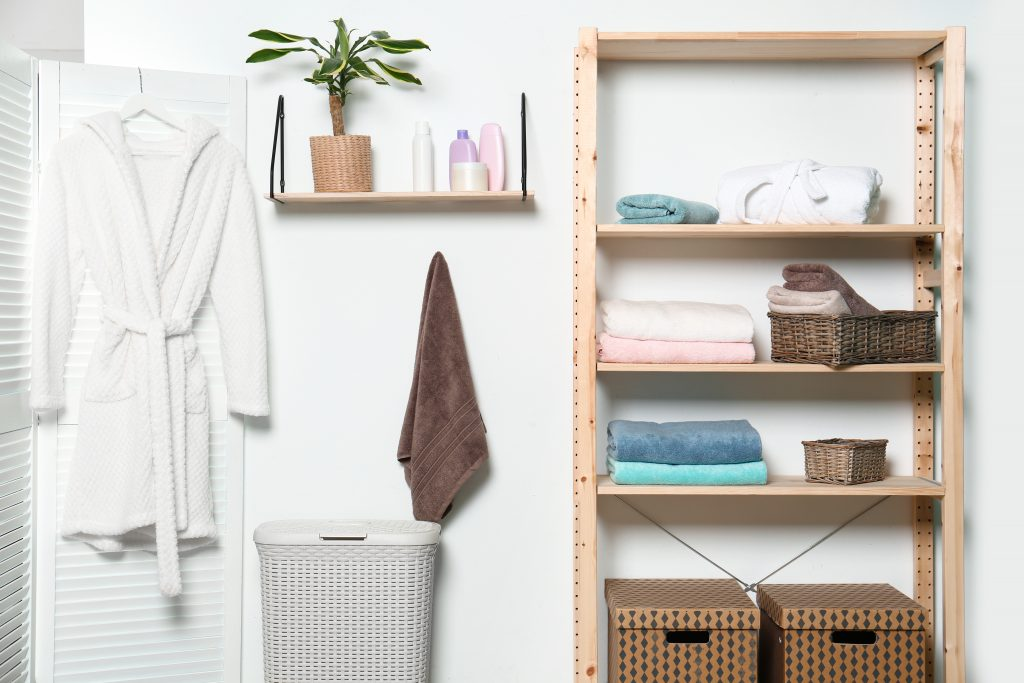 Clean towels and robe near white wall in modern bathroom interior