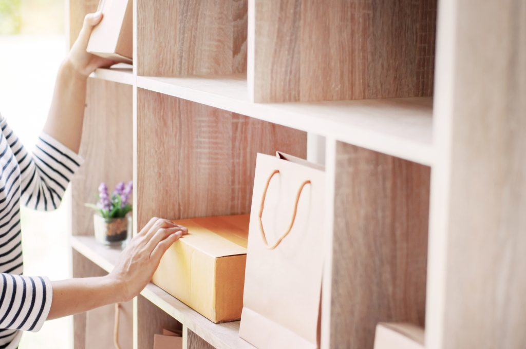 woman put a box in shelf at home office store