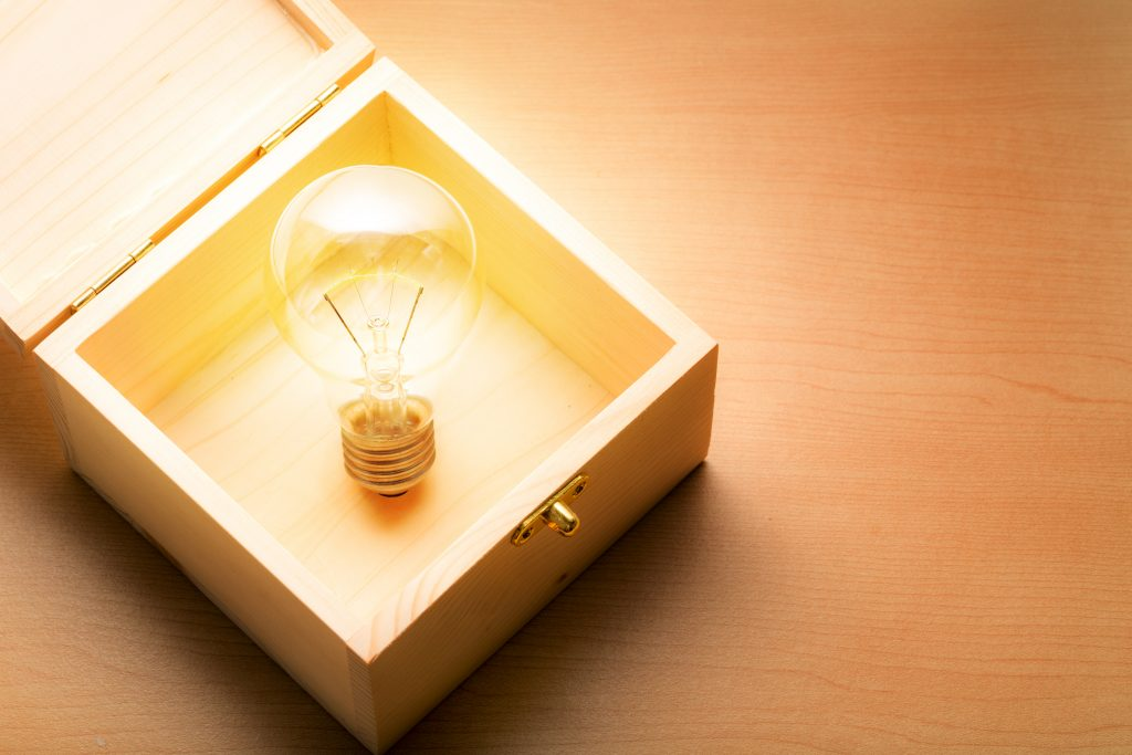 Light bulb in a wood box on wood background, old idea in a box can make the diffirent on a modern world concept