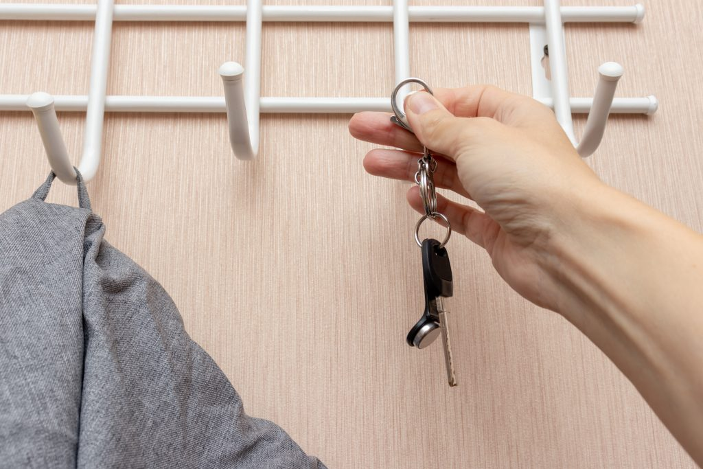 Woman hand hanging keys on a ring on a coat rack hook in a hallway, anteroom at home, home safety and security concept