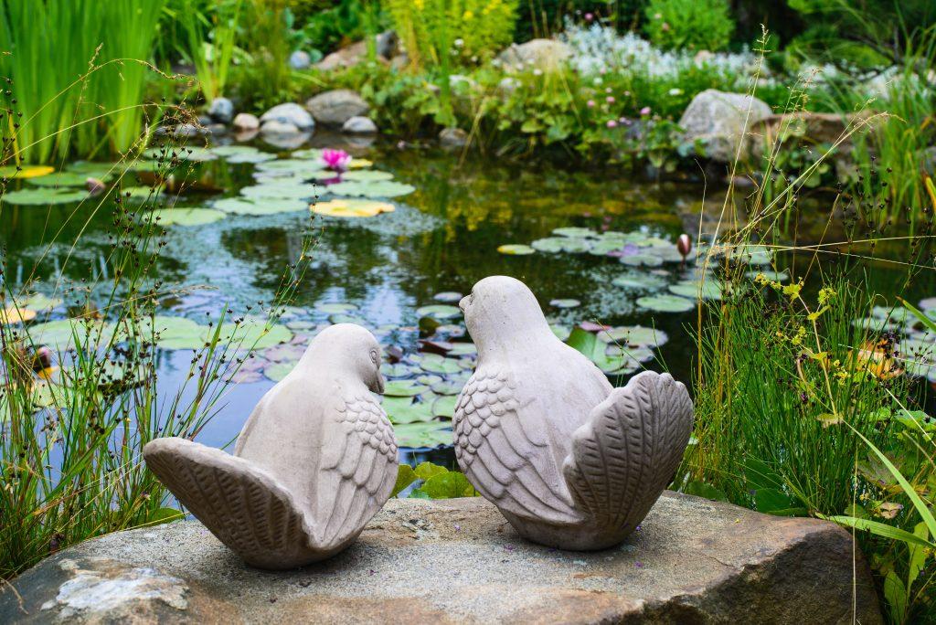 A couple of birds - garden sculpture against a pond