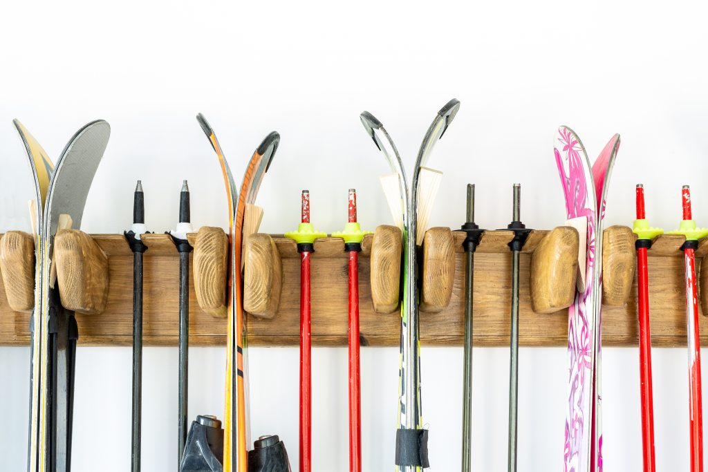 Lot of ski hanged on customized wooden wall mount at garage for seasonal storage. Extreme winter sport equipment handling at home warehouse