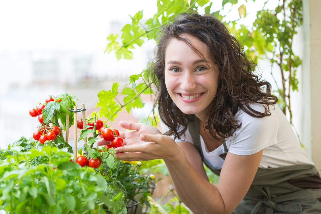 Young woman taking care of her plants and vegetables on her city balcony garden - Environment and ecology theme