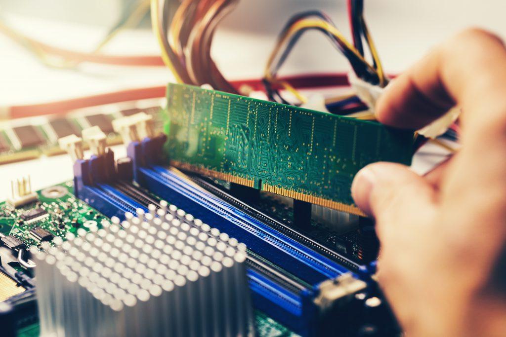 installing ram memory module on desktop computer motherboard closeup