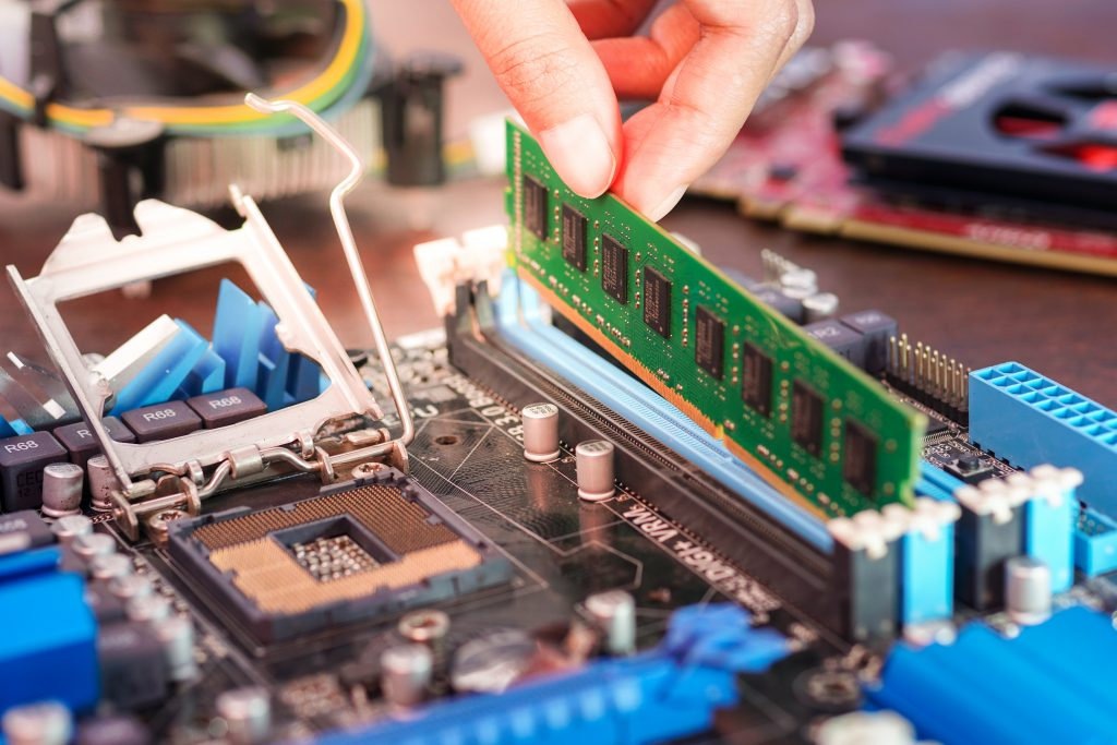 Engineers are placing the RAM on the sockets of the computer motherboard.
