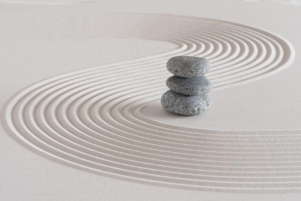 Japanischer Zen-Garten mit Steinen in strukturiertem weißem Sand