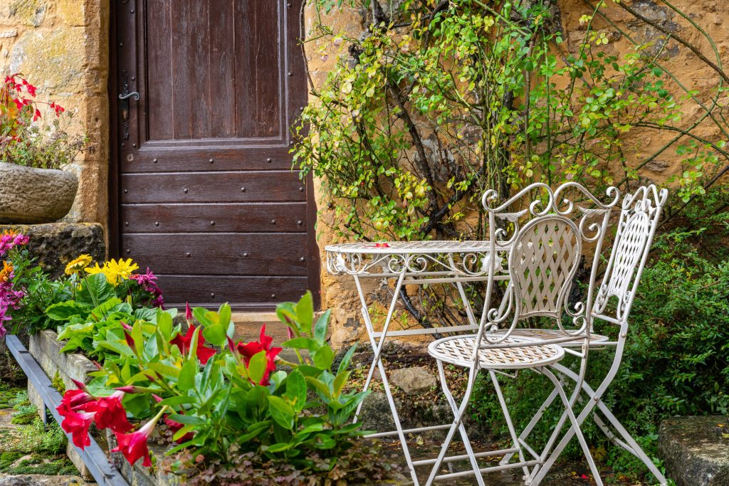 Cosy garden near the old stone house in the village. Beynac-et-Cazenac. France. Decoration of the home garden in the courtyard of the village house.