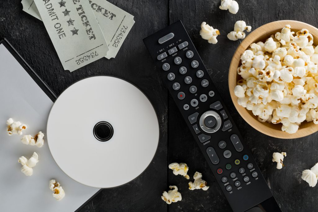 DVD or blu ray movie disc with tv remote control, movie tickets and bowl of popcorn on dark background. Home theatre movie or series night concept. Flat lay from above.