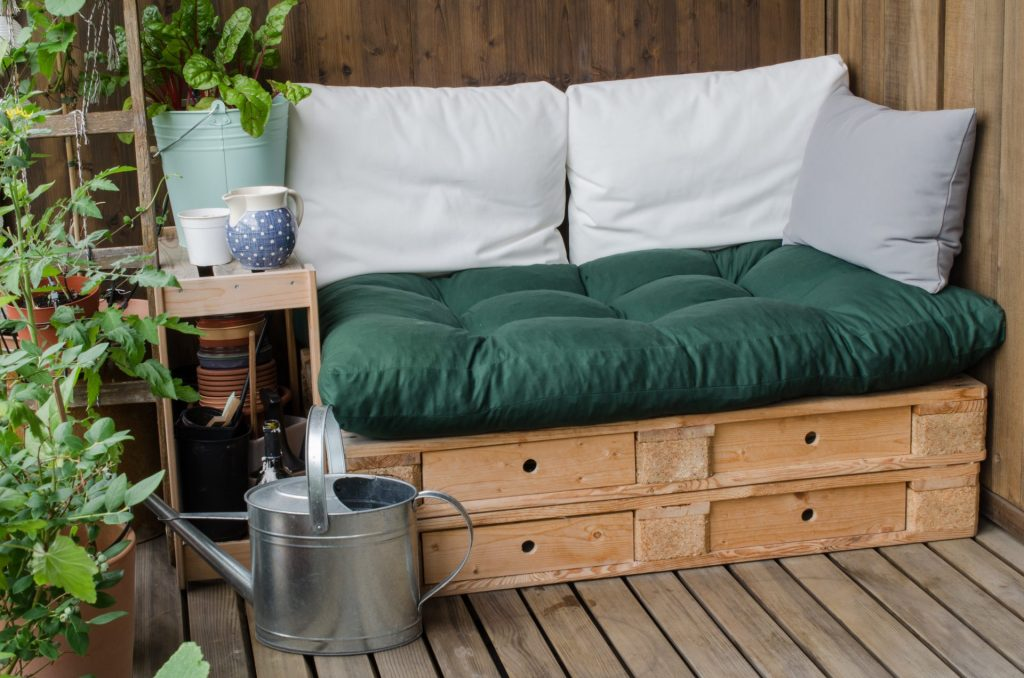 Cozy wooden pallet couch on balcony