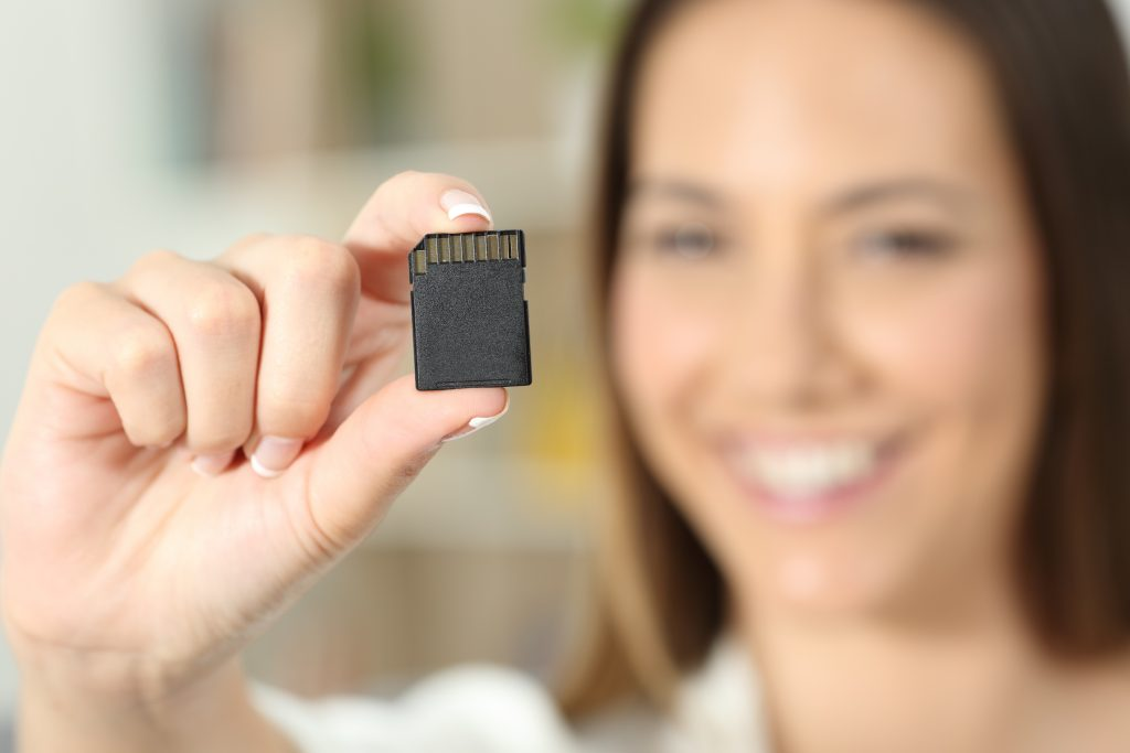 Happy woman hand showing a memory card