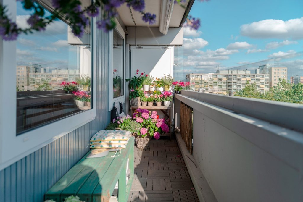 Spacious balcony bench with colorful flower pots in the corner