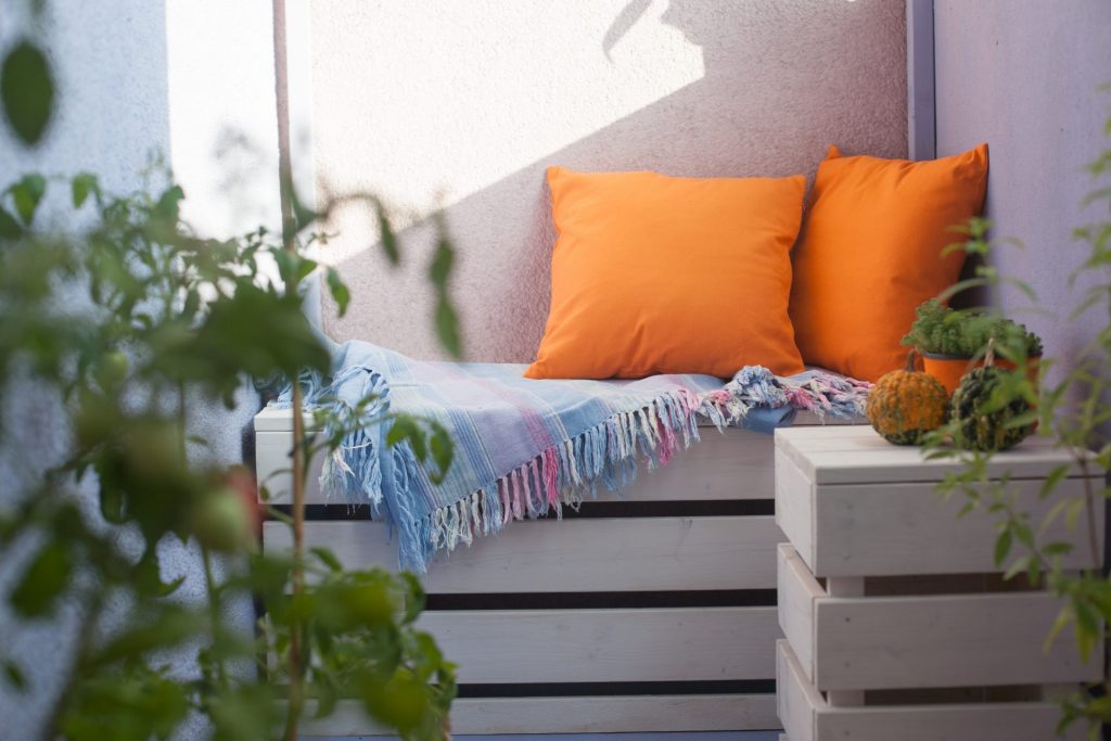 A blanket and cushions for an intimate corner on the balcony