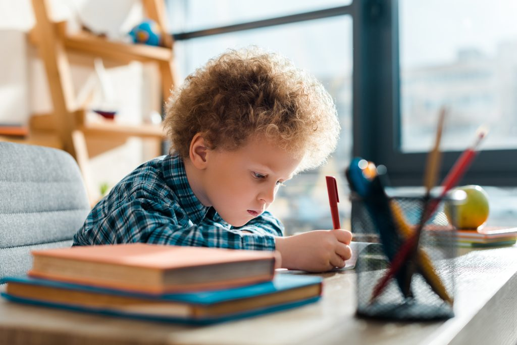 selective focus of curly kid writing near books