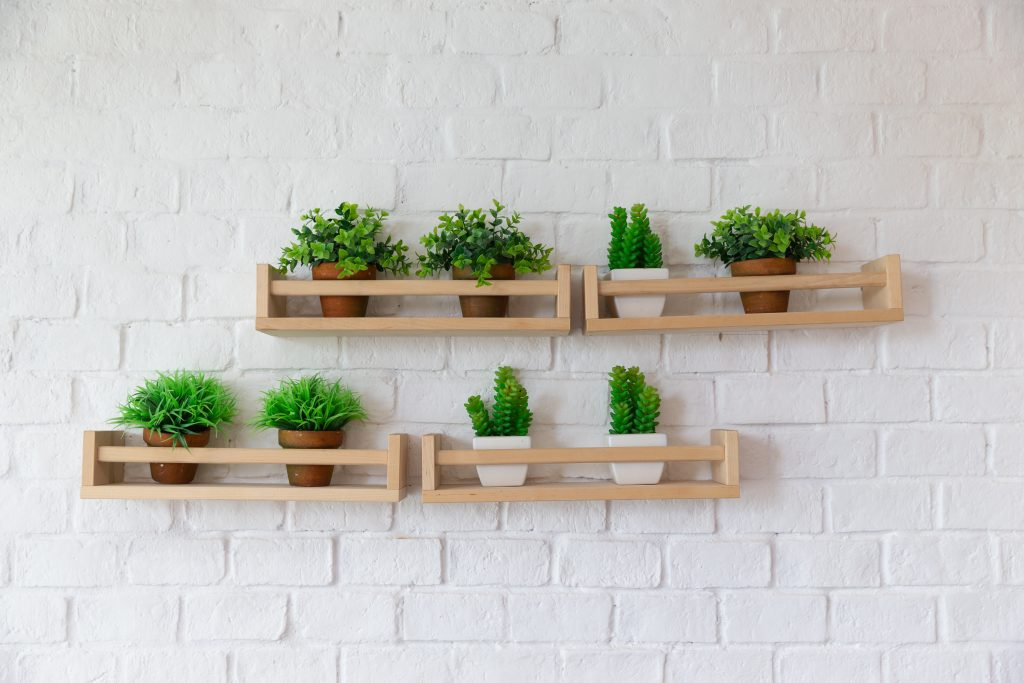 small plant pots placed on wooden shelf on white brick wall.
