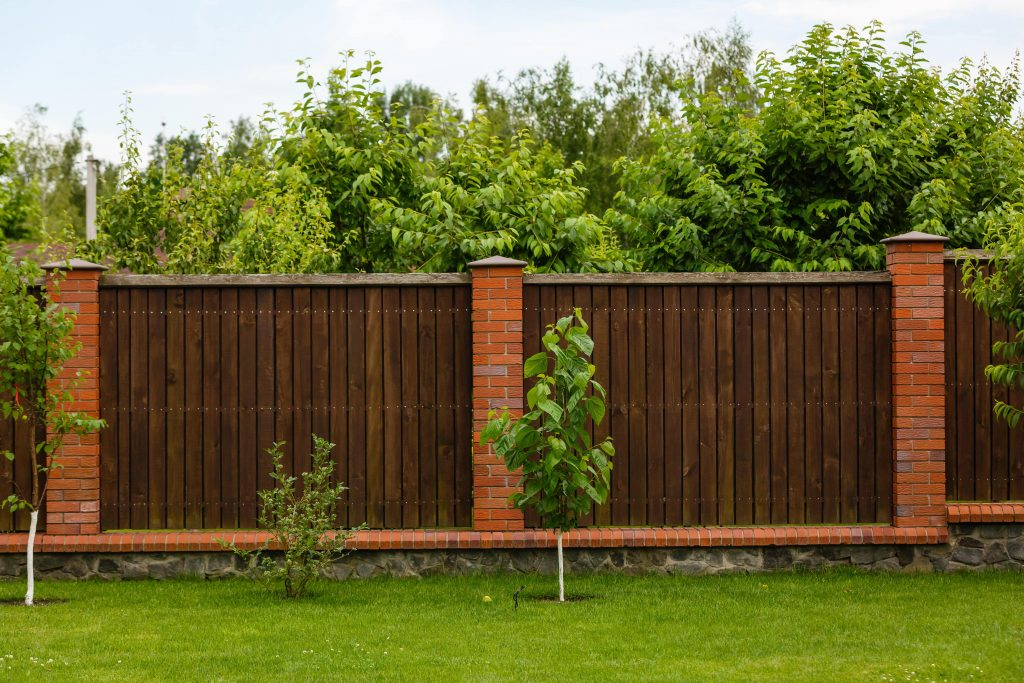 New wooden fence with massive stone brick pillars. Green lawn and trees, daytime