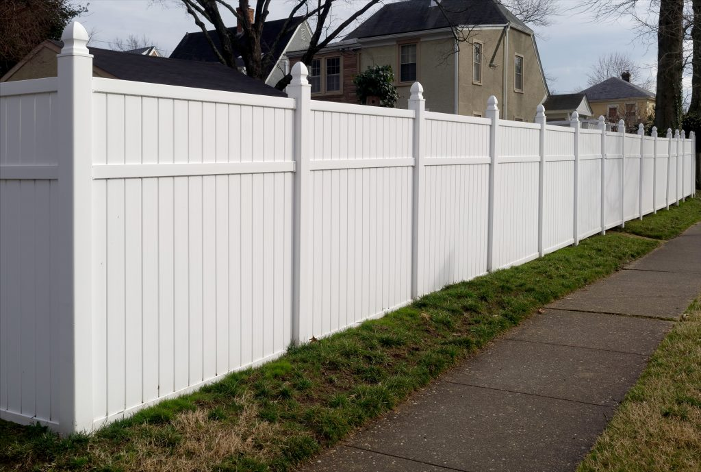 White vinyl fence in residential neighborhood.