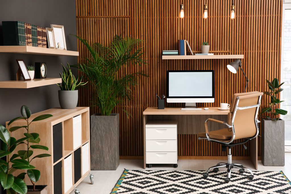 Comfortable workplace with computer near wooden wall in stylish room interior